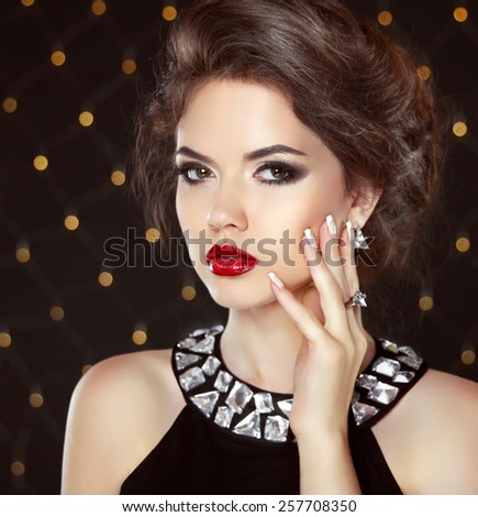 Stare. Beauty fashion girl portrait. Beautiful brunette woman model with makeup and hairstyle in earrings over bokeh lights background - stock photo