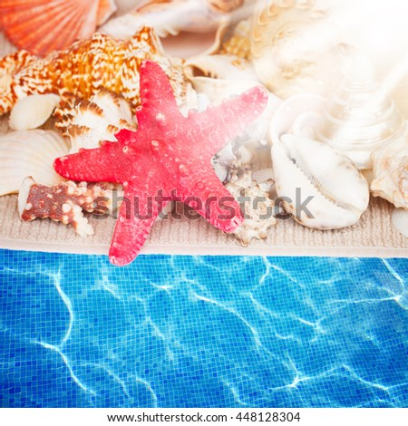 starfish and seashells on towel by pool water with sun rays - stock photo