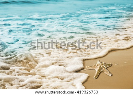 Starfish and soft wave on the sandy beach - stock photo