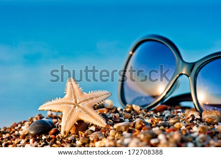 Starfish and sunglasses on the beach against the sea - stock photo
