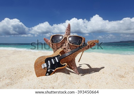 Starfish guitar player on sand of tropical beach at Philippines - stock photo