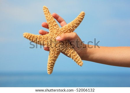 starfish in child's hand. focus on wrist. sea and sky in out of focus. - stock photo