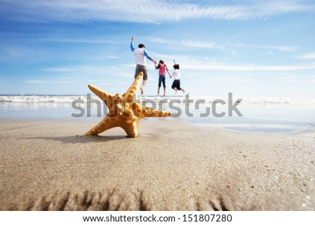 Starfish In Foreground As Father Plays With Children In Sea - stock photo