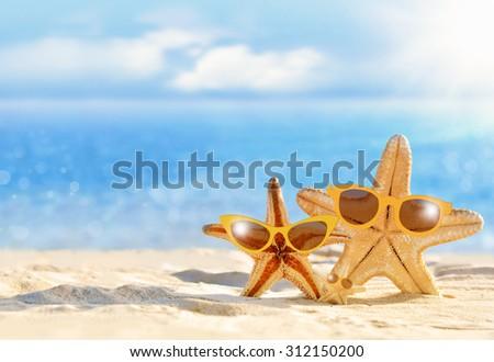 Starfish in yellow sunglasses on the summer beach - stock photo