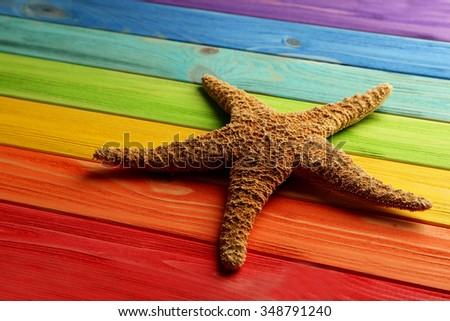 Starfish on a colorful wooden table - stock photo