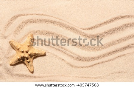 Starfish on sand with marks of waves. Summer beach background. View from above - stock photo