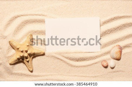 Starfish, scallop seashell and two stones with blank white visit card on beach sand. Summer beach background. View from above