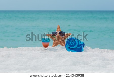 starfish standing between towel and cocktail in wine glass on white sand beautiful beach against tranquil ocean and blue sky on sunny warm summer day - stock photo