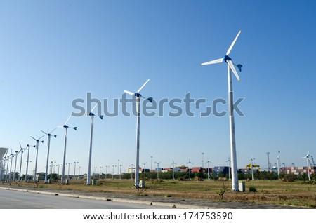 Stark White Electrical Power Generating Wind Turbines - stock photo