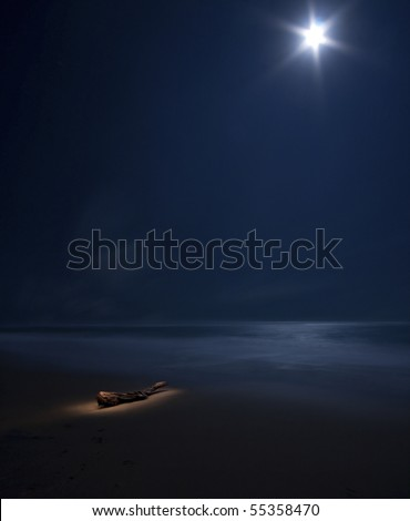 starry moon on night sea with beach and tree trunk painted with light - stock photo
