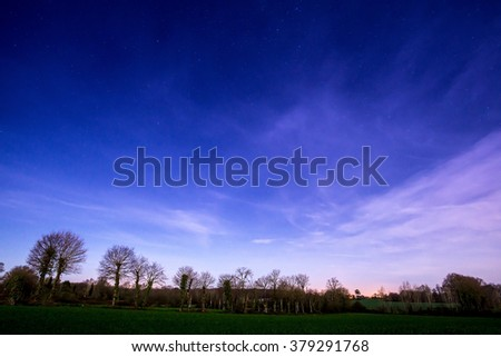 starry sky above the clouds lighted up by a village hidden by trees bordering a field in the french countryside during winter - stock photo
