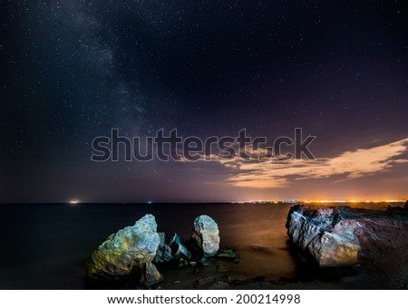 Stars and sea. Night view of the sea cliffs on the night sky. Shining stars and the Milky Way. Aside sparkles night city metropolis - stock photo