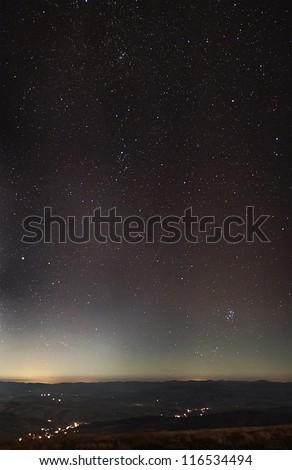 Stars over city lights and cloudy mountains panorama under moonlight - stock photo