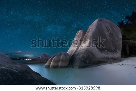 Stars with Milky Way over famous granite boulders at Anse Source d'Argent beach, La Digue island, Seychelles. - stock photo