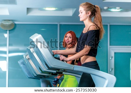 Start exercising. Sport and slender girl running on a treadmill and configures the simulator. Athlete dressed in sports uniforms and running in the gym. - stock photo