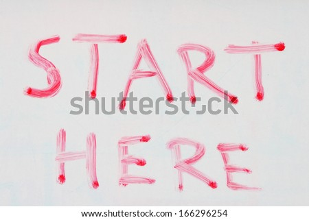 start here written in red dry erase marker on a used white board - stock photo