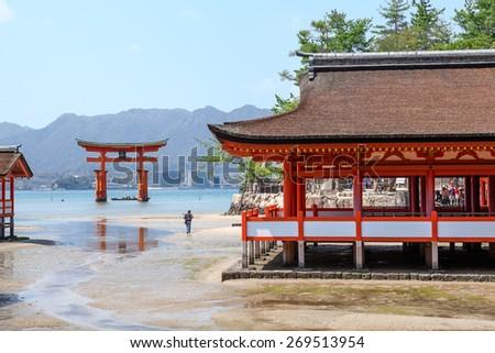 Start low tide at Itsukushima Shinto shrine, the sacred red torii in shallow water. Miyajima Island, Japan - stock photo