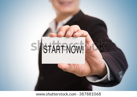 Start now message word on card in hand of Friendly man hand and smiling