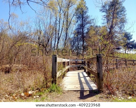 Start of a wooden bridge to lead over a pond in the park - stock photo