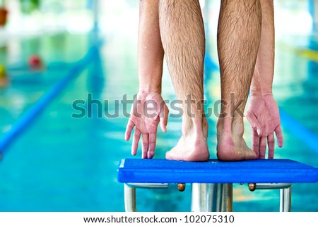 start swimming race concept with male swimmer in swimming pool - stock photo