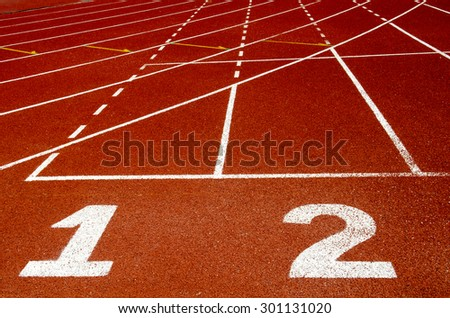 Start track. Lanes 1 2 of a red racing track - stock photo