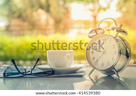 Start up concept.Coffe cup,alarm clock,newspaper,books,glasses.morning coffee day start.Education business place, vintage tone - stock photo