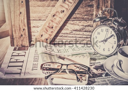 Start up concept.Tea cup,alarm clock,newspaper.morning tea day start.Education business place, vintage tone - stock photo