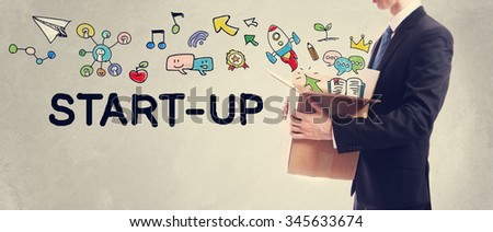 Start-Up concept with Businessman holding a cardboard box - stock photo
