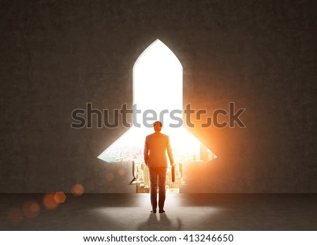 Start up concept with businessman holding briefcase and standing in front of rocket shaped gap in wall, revealing sunlit New York city view - stock photo