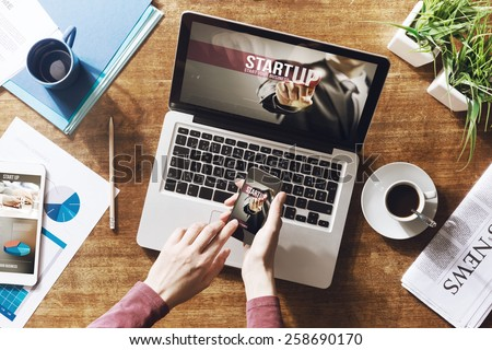 Start up website on laptop, touch screen tablet and smartphone on a desktop - stock photo
