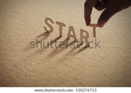START wood word on compressed board with human's finger at T letter