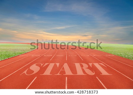 Start written on Running track with green grass and blue sky white cloud background
