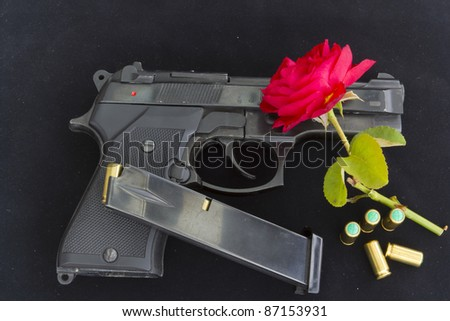 Starter pistol with bullets and a rose - stock photo