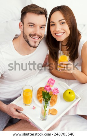 Starting a good day with breakfast in bed. Top view of beautiful young loving couple having breakfast in bed and smiling   - stock photo