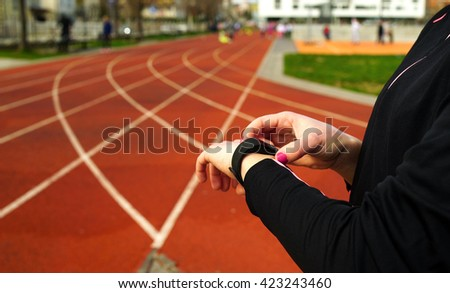 Starting a run with fitness activity tracker bracelet. Female caucasian jogger on running tracks. - stock photo