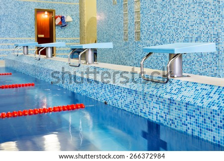 Starting blocks and lanes in public swimming pool - stock photo