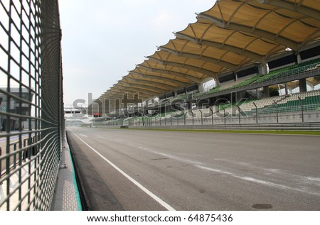 Starting & finishing point  of a race track with patron grandstand alongside. Concept of spectatorship for decisive sport moments. - stock photo