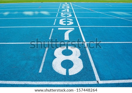 Starting line in outdoor stadium with blue asphalt and white markings - stock photo
