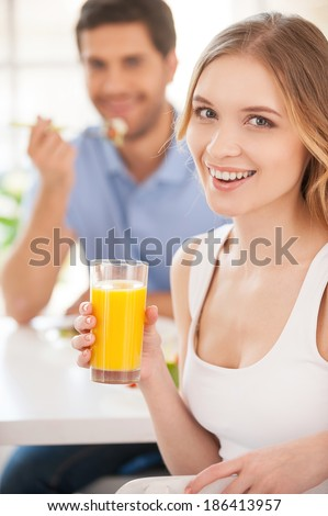 Starting morning together. Handsome young woman holding a glass of orange juice and looking over shoulder while having breakfast with his girlfriend