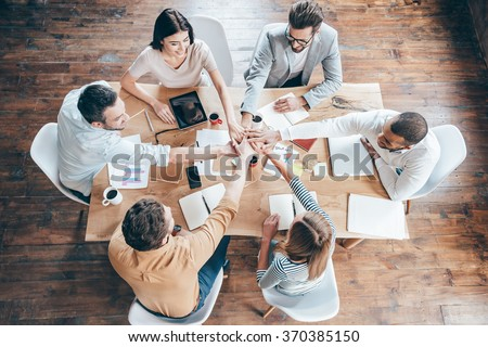 Starting new working day as a team. Top view of group of six young people holding hands together and smile while sitting at the office desk - stock photo