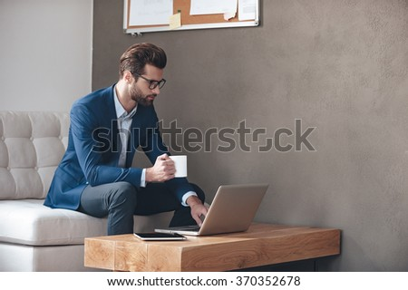 Starting new working day. Handsome young man wearing glasses holding coffee cup and working with laptop while sitting on the couch in office - stock photo