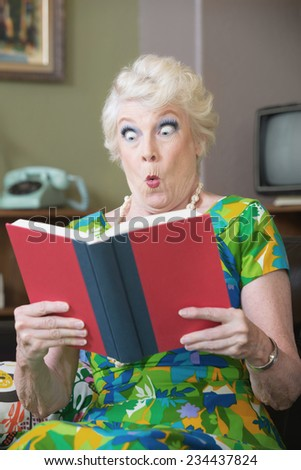 Startled Caucasian woman reading hard cover book - stock photo