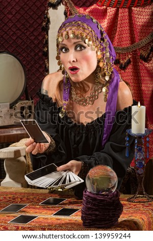 Startled tarot card reader with crystal ball and candle - stock photo