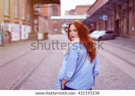 Startled young redhead woman looking back over her shoulder at the camera as she strolls down a deserted urban street - stock photo