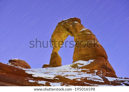 Startrails and Delicate Arch in Arches National Park, Utah in winter - stock photo