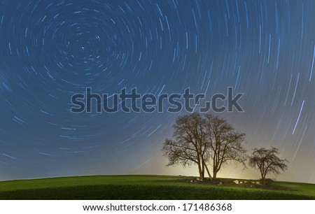 Startrails with trees. Long exposure visualizies the move and dynamics. - stock photo
