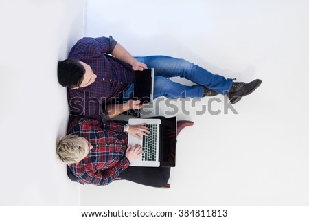 startup business and new mobile technology concept with  young couple in modern bright office interior working on laptop and tablet computer on new creative project and brainstorming, aerial top view