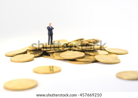 Startup business concept. Businessman thinking or making decision with pile of saving money coin. - stock photo