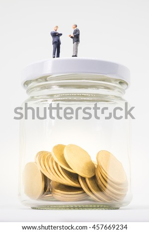 Startup business concept. Businessmen talking and making decision with saving money coin in glass jar. - stock photo