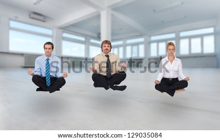Startup business - young business people meditating in empty office space - stock photo